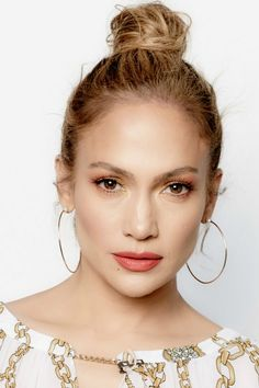 Jennifer Lopez's copper-red eyeshadow, dark pink lipstick, and topknot