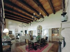 The open floor plan of this Old World Spanish-style interior allows for fluidity and simple design. The wooden ceiling beams previously used as supports now offer a decorative element. Round candle chandeliers and the arched doorway complete the Old World Spanish look. Design by Keith Summerour of Summerour Associates & Architects