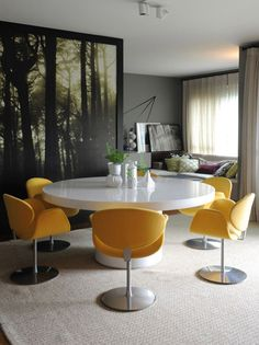 Oversized art in graphic black and white, paired with the buttercup yellow chairs, makes a bold statement in this room.
