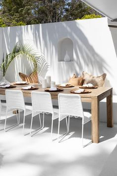 How stunning is this white rendered wall paired with Uniqwas range of outdoor patio dining table and chairs! We are loving this coastal style Byron Bay Farmhouse filled with Uniqwa Furniture Pieces! Herringbone Dining Table, Gonubie Outdoor Dining Chair White, Senegal Cushion Cover and teak carved plates. © Uniqwa Furniture Collections Styling @uniqwacollections @villastyling Photography @villastyling Location @nirvanahouse.byronbay