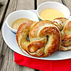 Homemade soft pretzels with two sauces: sweet mustard and sharp cheddar cheese.
