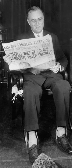 Franklin Delano Roosevelt seated in a chair holding a newspaper showing headline, 'Roosevelt wins by 735,000; Democrats Sweep Congress'