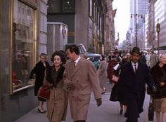 """Elizabeth Taylor and Laurence Harvey stroll up Fifth Avenue for a location shot in the film """"Butterfield 8"""" (1960). The view is to the south from 55th Street & Fifth Avenue."""