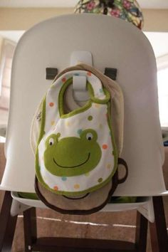 """""""Command"""" hooks on the back of high chair to hold bibs. Until your child takes them off. ;) we put a command hook inside our pantry instead"""