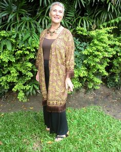 Authentic Indonesian batik women's kimono jacket. Gorgeous shades of plum and mauve set off against a gold backdrop and trimmed out in striking brown fringe. Dress it up, dress it down this kimono jacket will quickly become a favorite go to