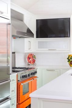 Leawood Colorful Kitchen - transitional - This pop of orange with the stove and the white and greenish/white cabinets are just beautiful.  And of course, subway tiles are always stunning!