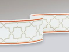 Meknes Border A beautiful wide width tape embroidered with large scale interlocking shapes shown in greige and vibrant orange on a white ground. The design is inspired by the zelig tile borders of North Africa.