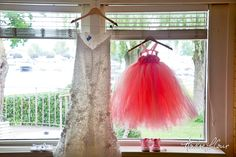A lacy wedding gown with a pair of hearts stitched inside and the bride's little girl's outfit for the big day   Andre LaCour Photography