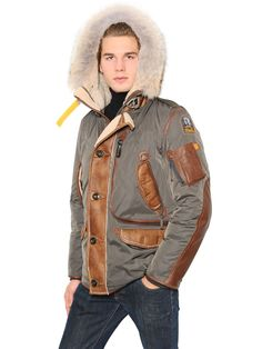 Non-detachable hood with detachable coyote fur trim. Shearling hood, placket and pocket flaps . Front button and concealed two-way zip closure with heavy duty metal hook. Ribbed cuffs. Leather trim, pocket and sleeve inserts . Logo patch on sleeve . Zipped side slit . Elastic waistband . Four front flap pockets. Two front zip pockets. One large zip pocket . One sleeve zip pocket . Two internal mesh pockets . Down feather filling. Sample size: L