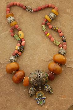 """Berber Tribe Necklace. The Berbers of Northern Africa are known from their exquisite silver jewelry decorated with green and yellow enamel. The Hand of Fatima and two barrels dangle from the large Berber """"egg"""" that is the focal point of this piece. Large copal amber beads, Venetian trade beads, smaller Berber and amber beads and coral-colored glass complete the strand. Length: 26"""" The silver clasp is handcrafted by Balinese artisans.  http://www.nanstine.com/text/p-berber-tribe.html"""