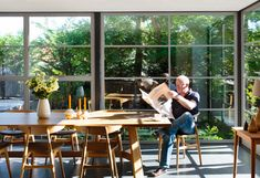 AT HOME IN CANBERRA - glass and steel conservatory - dining area furnished with Wegner Wishbone Chairs and CH33 Chairs #Globalhomes by Carl Hansen & Søn