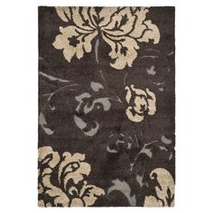 Anchor your living room seating group or define space in the den with this lovely shag rug, featuring a scrolling floral motif in dark brown.  ...