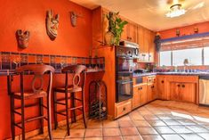 The rust and blue in this kitchen is so warm and energizing! Love the saltillo tile flooring. #casascolonialesdeunpiso
