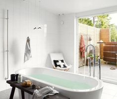 An indoor tub feels as if it is outside in its bright white light-soaked room