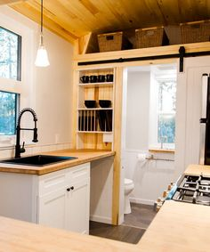The kitchen sits on a raised platform and it's outfitted with a full size freestanding gas range, refrigerator, and a full height tile backsplash behind the range.