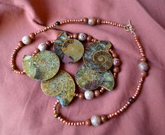Five ancient ammonite fossils strung with carved soapstone, copper pyrite, tiger eye & goldstone, finished with a 24k gold filled clasp.
