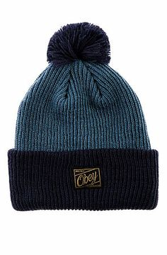 The Old Timey Pom Pom Beanie in Mineral Blue and Navy by Obey. This fold-over beanie features a two-tone colorway with a logo tag on the front fold and a pom detail on top. $25