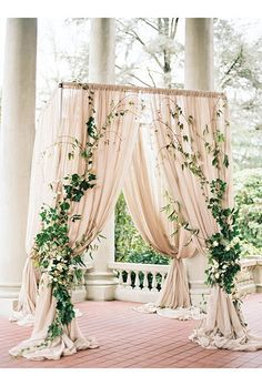 Billowing taupe drapes adorned with climbing ivy make for a romantically dramatic ceremony arbor.