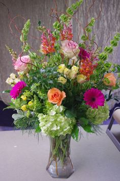 Tall vase arrangement featuring gerber daisies, hydrangeas, long-stem roses, spray roses, bells of Ireland, snapdragons, bupleurum, and curly willow.