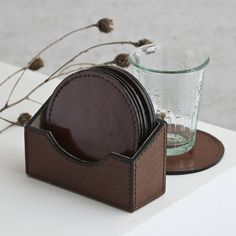 A set of six round leather coasters complete with a stacking holder. Perfect protection for polished wood surfaces, this set of six leather coasters stand neatly in their matching holder. Lower at the front, and supporting at the back, the holder displays the coasters when they are not in use. The grain of the leather adds a distinguished feel to this useful gift. They are leather on both sides so suitable for all surfaces. Matching leather placemats are also available.LeatherCoasters 10cm…