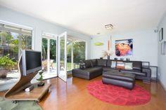 idées aménagement salon - support TV en bois de design organique, tapis rond en rouge et canapé en cuir noir