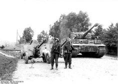 "Panzerkampfwagen VI Tiger I Ausf.E ""B12"" from 11. Kompanien/III.Abteilung/Panzer-Regiment 'Großdeutschland', passes close to a Russian anti tank guns 76 mm M1942 (ZiS-3) on the road, while two Obergefreiter watching the sky."