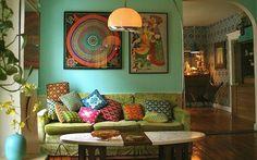 Love the look! Mooie turquoise muur met gekleurde schilderijen en een oude bank met vrolijke kussens