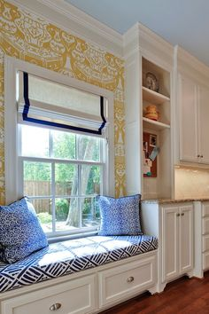 Kitchen window seat | David Hicks The Vase Wallpaper in Yellow | Blue painted ceiling | Vertical built-in cabinets | Quadrille Fabrics China Seas Macoco II Navy on Tint Fabric | White w/navy blue grosgrain roman shade