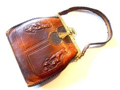 Arts and Crafts 1920s carved leather bag with deco details. Whip stitch leather around edges and handle. Comes with teensy Indian Head coin purse.