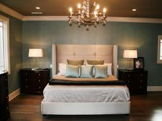The creamy, beige tufted headboard maintains the straight and simple lines of this modern space. Subtle shine is added with icy-blue tones in the wall color and bed linens.  Contrasting chocolate-brown nightstands make the pale hues pop.
