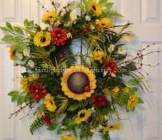 """Sunflower Heaven Wreath says that summer is here. It is full with sunflowers, daisies, red zinnias, mini bell flowers, and other wildflowers. We love the """"Welcome"""" sunflower metal sign with ladybugs.  The base is a grapevine wreath. The measurements are 37x36x9 tip to tip. $126.50"""