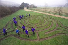 School children in uniform walking a labyrinth. This shot is interesting. The labyrinth is on the private land of Adrian Fisher the worlds leading maze designer and is one of two mazes he has.