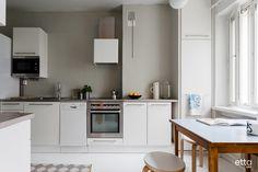 Valkoisen keittiön taustaseinän kaunis sävy tulee kauniisti esiin valkoisen rinnalla. Moderniin keittiön vanha pöytä tuo kerroksellisuutta tilaan.