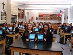 A highschool classroom posing for a picture with their tablets showing.