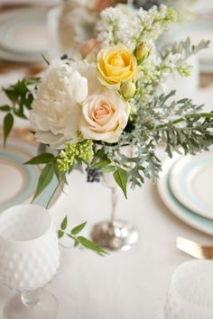 Pastel arrangement with blush and buttercup yellow roses, peonies and dusty miller.