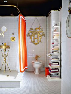 One of my favorite chic bathrooms ever. White subway tile takes a ride with antique brass fixtures/Hermes decor, bittersweet chocolate, and a slice of orange.