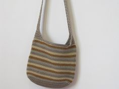 Cute 90s crochet striped shoulder bag with zipper closing. Inside is fully lined with beige fabric. Small inside pocket with zipper closing. Botton of purse has rectangle shape  Colors: taupe, beige, caramel,grey  Perfect size to carry all your necessities.  Material: feels like polyester yarn  Measurements: Width 10 Height 8 Strap drop 21  Vintage condition: good ****Item has been washed before shipping.  (purse is machine washable in cold water- delicate cycle and hang to dry) Ships out in…
