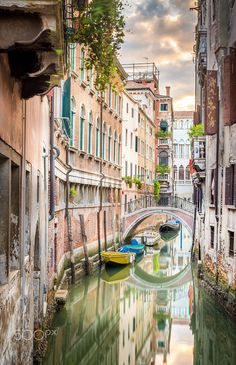Beautiful narrow canal with silky water in Venice, Italy