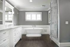Bathroom by Michaelson Homes LLC. Dark floors, light cabinets, Carerra