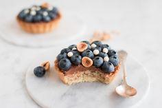 Smørsprøde tærtebunde med cremet kokosfyld og en topping af hasselnøddesmør med chokolade samt masser af friske blåbær. Kræs for kageelskere!