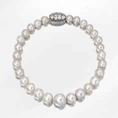 A Single Strand Natural Pearl and Diamond Necklace, Cartier, Paris Composed of 28 natural pearls graduating from approximately 16.8 to 9.2 mm., completed by an oval clasp set with 2 emerald-cut diamonds weighing approximately 2.00 carats and 2 fancy-shaped diamonds weighing approximately 1.00 carat, bordered by 20 small round diamonds weighing approximately .70 carat, length 14 inches, clasp signed Cartier, Paris. Photo courtesy of Sotheby's