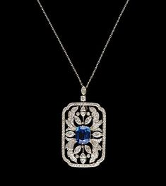 An antique Russian platinum, blue sapphire and diamond pendant/brooch by W.A. Bolin.