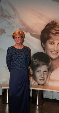 A wax figure of Diana, Princess of Wales with a photo of herself and Prince Harry in the background.