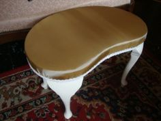 Vintage kidney shaped dressing table stool. Highly collectible. Near antique now but still strong and sturdy. Overpainted in creamy Ringwold Ground and waxed. Reupholstered with a piece of vintage gold satin and trimmed with ivory braid...
