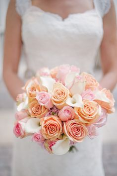 A bridal bouquet of popsicle pink and tangerine roses, and vanilla calla lilies