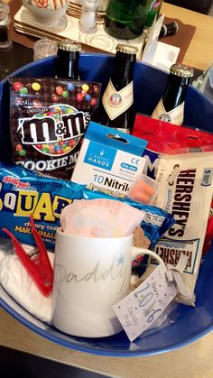 Daddy Survival Kit! Blue plastic bucket filled with gifts for a new father including chocolate, beer, nappies, ear plugs and a peg
