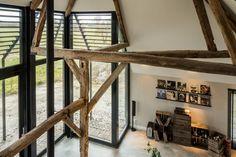 Het uitzicht vanuit de studie boven de keuken. De horizontale houten lamellen zorgen ervoor dat de zomerzon niet te diep in de woning kan komen. Bovenop heb je rust en extra mooi uitzicht op het interieur en de oude houten spantenstructuur.