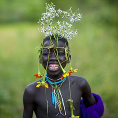 Surma tribe kid with flowers decoration - Omo Ethiopia by Eric Lafforgue.that beautiful smile!