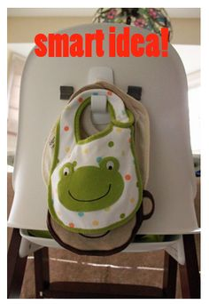 Put a Command hook on the back of the high chair for hanging bibs. Also for hanging diaper caddy/organizer on the wall or on sides of changing table