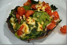 4 large portabella mushroom caps 1 large tomato, chopped 3 handfuls of fresh spinach 1/2 cup crumbled feta cheese 1/2 cup shredded mozzarella cheese Red pepper flakes Pepper 1/2 cup Italian dressing 1/4 – 1/2 cup chicken (beef or vegetable – for vegetarian) broth
